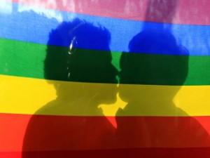 Dve osebi se poljubljata za mavrično zastavo.